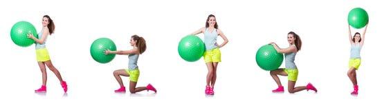 A jovem mulher com bola que exercita no branco fotos de stock royalty free