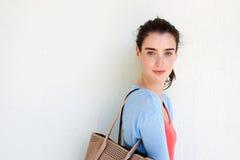 Jovem mulher com a bolsa contra a parede branca Imagens de Stock