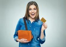 Jovem mulher com a bolsa que guarda o cartão de crédito do ouro fotografia de stock royalty free