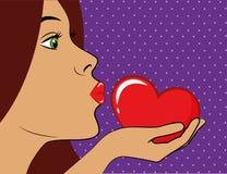 A jovem mulher com bordos vermelhos beija um pop art vermelho do coração ilustração stock