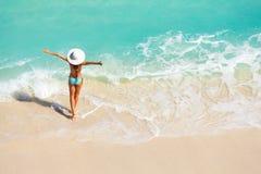 Jovem mulher com braços distante na praia da areia fotos de stock royalty free