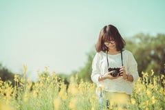 Jovem mulher com a câmera no jardim do Sunhemp Fotos de Stock Royalty Free