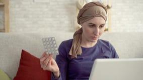 A jovem mulher com câncer em um lenço após a quimioterapia com os comprimidos em sua mão usa um fim do portátil acima vídeos de arquivo
