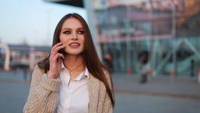 A jovem mulher com cabelo longo anda ao longo da rua e fala no telefone vídeos de arquivo