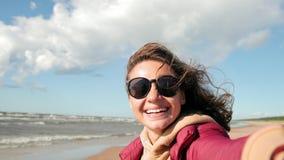 A jovem mulher com cabelo longo está tomando um selfie na praia, sopros de um forte vento vídeos de arquivo