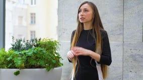 Jovem mulher com cabelo longo que gesticula ativamente ao dar uma conversa do suporte acima filme