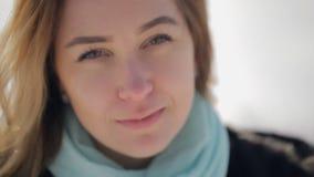 A jovem mulher com cabelo louro e o lenço azul olha diretamente, filme