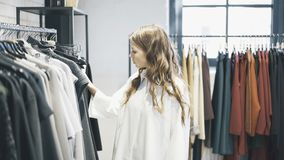 A jovem mulher com cabelo marrom está escolhendo a roupa comprar Imagem de Stock Royalty Free