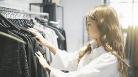 A jovem mulher com cabelo marrom está escolhendo a roupa comprar em uma loja Fotos de Stock