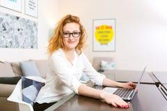 A jovem mulher com cabelo vermelho longo na camisa branca e vidros para a visão trabalha, olha a câmera, usa o portátil cinzento  foto de stock