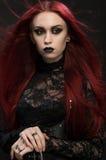 Jovem mulher com cabelo vermelho no traje gótico preto fotografia de stock royalty free