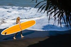 Jovem mulher com caminhada da prancha na praia preta da areia imagem de stock royalty free