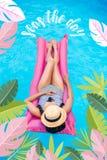 Jovem mulher com a cara da coberta do chapéu de palha que flutua no colchão de ar na piscina imagem de stock