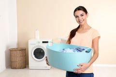 Jovem mulher com a cesta de lavanderia perto da máquina de lavar em casa fotografia de stock