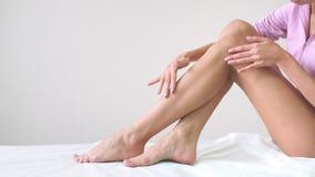 A jovem mulher com corpo perfeito está sentando-se com pés de seda lisos após a depilação Conceito da depilação, pele lisa filme