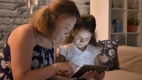 Jovem mulher com a criança que usa a tabuleta e sentando-se no sofá na casa moderna, conceito de família, dentro video estoque