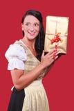 Jovem mulher com dirndl e um grande presente à disposição Fotos de Stock