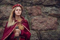 Jovem mulher com espada à disposição no fundo da parede de pedra Com espaço da cópia fotografia de stock royalty free