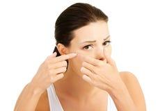 Jovem mulher com a espinha em sua cara. Tentativa espremê-la. Fotos de Stock Royalty Free