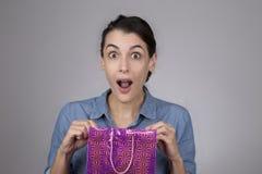 jovem mulher com expressão surpreendida em sua cara como abre o saco do presente Fotografia de Stock Royalty Free