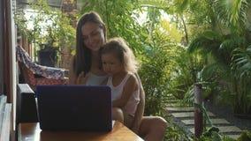 Jovem mulher com a filha bonito pequena que usa o portátil junto no movimento lento video estoque