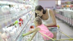 Jovem mulher com a filha bonito que escolhe um iogurte na alameda de compras na mercearia filme