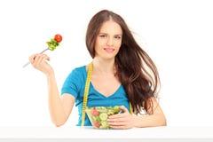 Jovem mulher com a fita de medição que senta e que come uma salada Foto de Stock