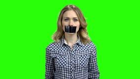 Jovem mulher com a fita preta sobre a boca video estoque