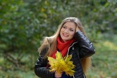Jovem mulher com folhas de outono à disposição Imagens de Stock Royalty Free