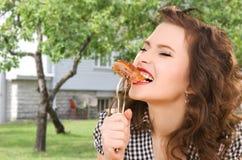 Jovem mulher com fome que come a carne na forquilha sobre a casa imagens de stock royalty free