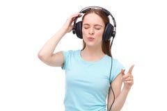 Jovem mulher com fones de ouvido que escuta a música e a dança Fotos de Stock