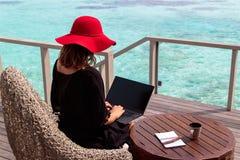 Jovem mulher com funcionamento vermelho do chap?u em um computador em um destino tropical foto de stock