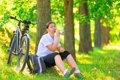 Jovem mulher com a garrafa do descanso da água Foto de Stock