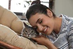 Jovem mulher com gato bonito em casa fotografia de stock royalty free