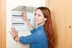 Jovem mulher com interruptor da luz na casa imagem de stock