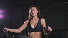 Jovem mulher com máquina elíptico filme