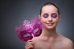 A jovem mulher com máscara do carnaval fotografia de stock royalty free
