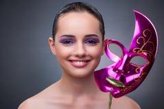 A jovem mulher com máscara do carnaval fotografia de stock