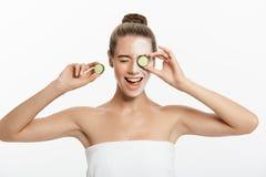 Jovem mulher com a máscara facial da argila que mantém fatias do pepino isoladas no fundo branco fotos de stock royalty free