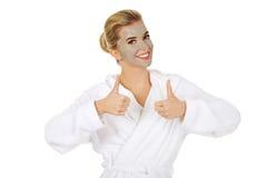 A jovem mulher com máscara facial mostra o sinal APROVADO fotografia de stock