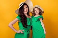 Jovem mulher com mão na cintura que está com filha pequena Imagem de Stock Royalty Free