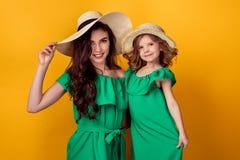 Jovem mulher com mão na cintura que está com filha pequena Imagens de Stock