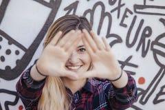 Jovem mulher com mãos junto na parte dianteira que quadro seu olho fotos de stock