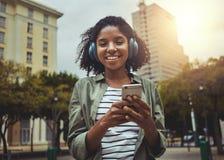 Jovem mulher com música de escuta do telefone celular através do fones de ouvido foto de stock royalty free