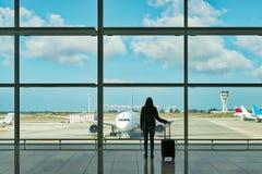 Jovem mulher com a mala de viagem no salão da partida no aeroporto conceito do curso imagens de stock
