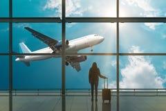 Jovem mulher com a mala de viagem no salão da partida no aeroporto conceito do curso foto de stock