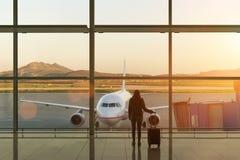 Jovem mulher com a mala de viagem no salão da partida no aeroporto conceito do curso imagem de stock royalty free