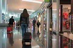 Jovem mulher com a mala de viagem no sal?o da partida no aeroporto conceito do curso imagem de stock royalty free
