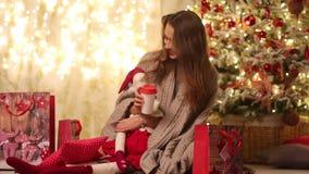 A jovem mulher com manta e Santa Claus senta-se ao lado dos pacotes da árvore e do presente de Natal, dos sorrisos e do café das  video estoque