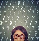 Jovem mulher com muitos pontos de interrogação acima de sua cabeça Foto de Stock